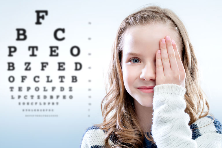 girl covering one eye next to eye test chart